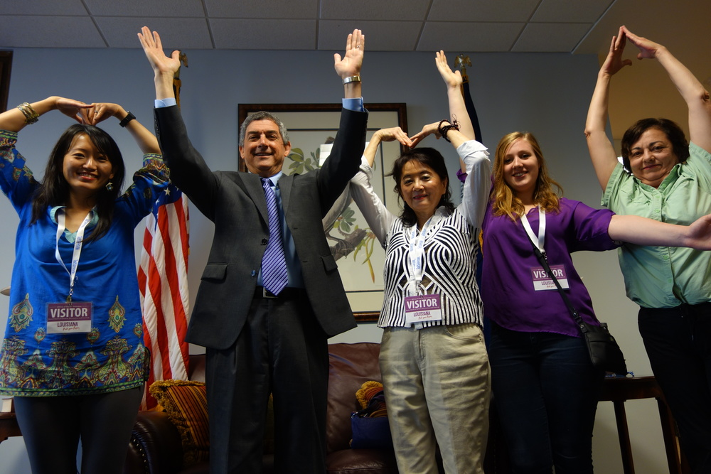 Stephanie Lusk, Lieut. Gov. Jay Dardenne, Marlene Yu, Iris MacLean, and Debra Credeur spell out MYM LA with their arms to celebrate the addition of the Marlene Yu Museum to Louisiana