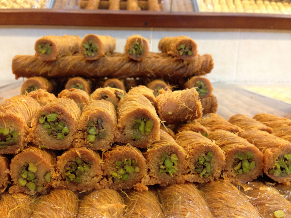 Baklava sitting scrumptiously for sale at a market.
