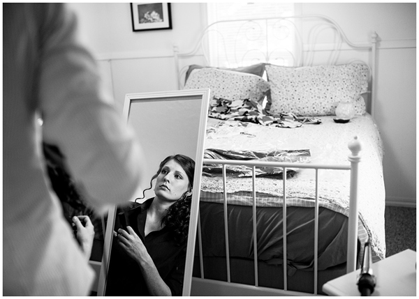 bride getting ready in mirror black and white