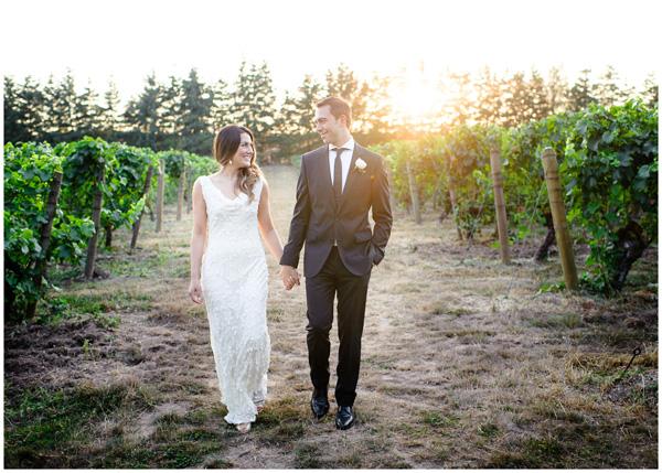 bride groom walking down vineyard during sunset