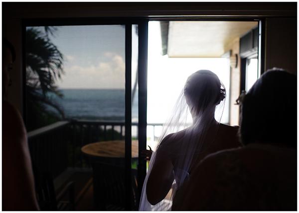 beautiful silouette of bride getting dress on in doorway kauai