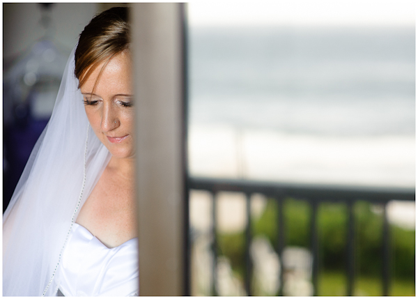 bride having dress adjusted in doorway reflection