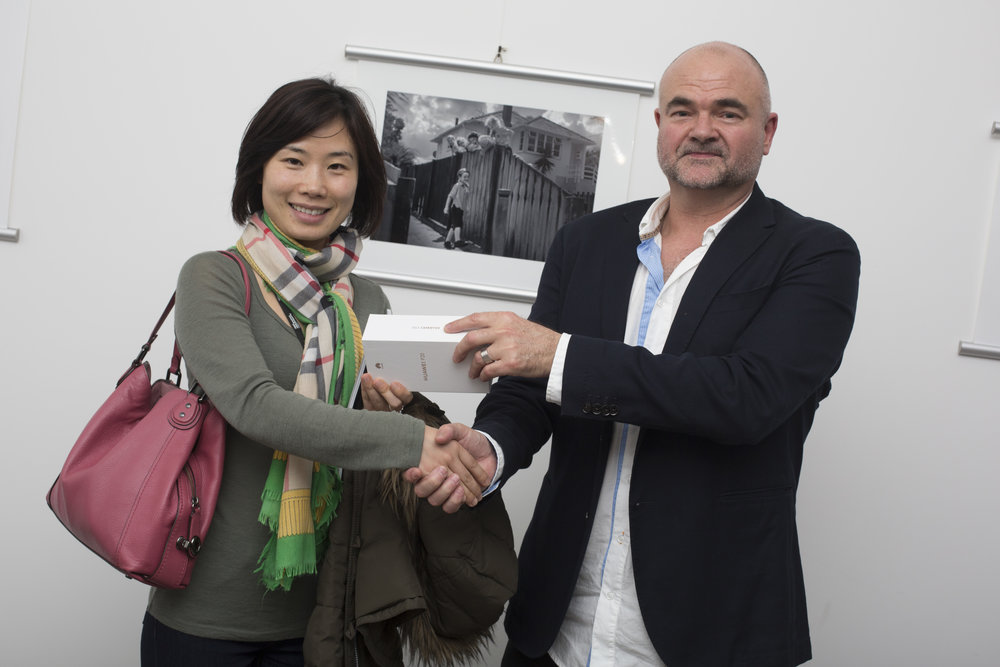 Daughter of second-placing Smartphone photographer, Bin Bai, accepts the Huawei P20 on his behalf