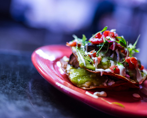 Mexi-Cali Tostadas - Pork belly and green mole tostadas layered with mixed cheeses and topped with pico de galla and Mexican crema.