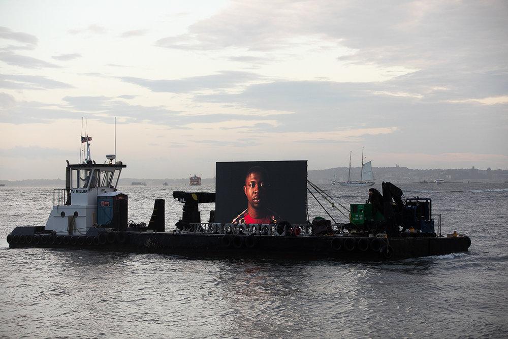 "©  Shimon Attie Night Watch (Edafe), Hudson River, Barge, Tugboat, 20' wide hi-res LED screen, 30""X45""/48""X72"" Lambda Photograph, Shimon Attie, 2018, courtesy of Jack Shainman Gallery, NY"