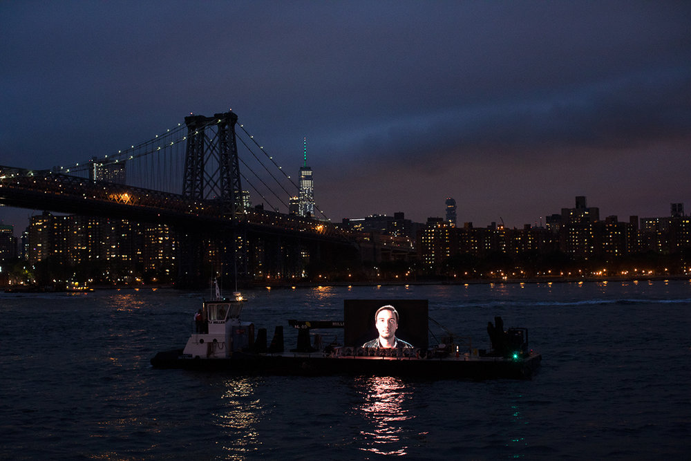 """©  Shimon Attie  Night Watch (Sergey with Bridge), East River , Barge, Tugboat, 20' wide hi-res LED screen, 30""""X45""""/48""""X72"""" Lambda Photograph, Shimon Attie, 2018, courtesy of Jack Shainman Gallery, NY"""