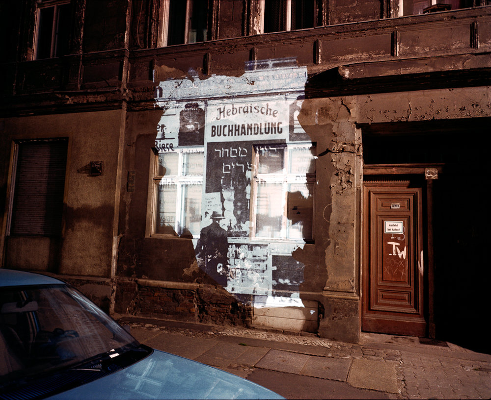 """©  Shimon Attie  Almstadtstrasse 43: Slide projection of former Hebrew bookstore, 1930 , Berlin, 1992, on-location installation at 1:1 architecture scale and 33""""X40"""" chromogenic photograph, from the project  The Writing on the Wall , courtesy of Jack Shainman Gallery, NY"""