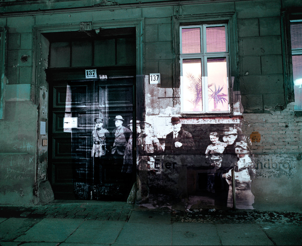 """©  Shimon Attie  Linienstrasse 137: Slide projection of police raid on former Jewish residents, 1920, Berlin , 1992, on-location installation at 1:1 architecture scale and 33""""X40"""" chromogenic photograph, from the project  The Writing on the Wall , courtesy of Jack Shainman Gallery, NY"""