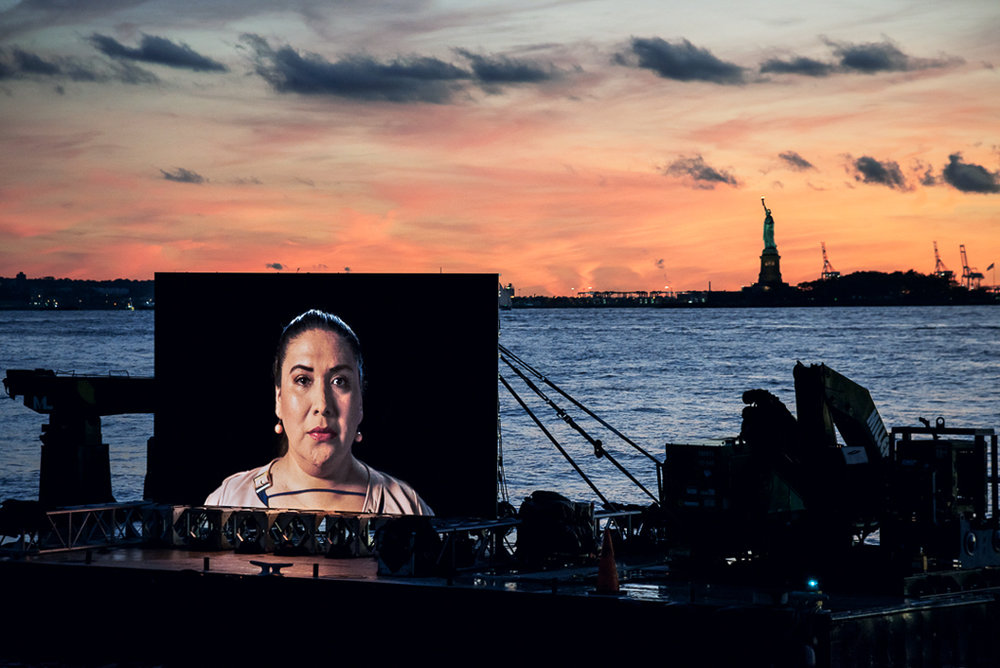 ©  Shimon Attie  Night Watch (Mikaela with Liberty), Hudson River ,  2018  Barge, Tugboat, 20' wide hi-res LED screen, courtesy of Jack Shainman Gallery, NY