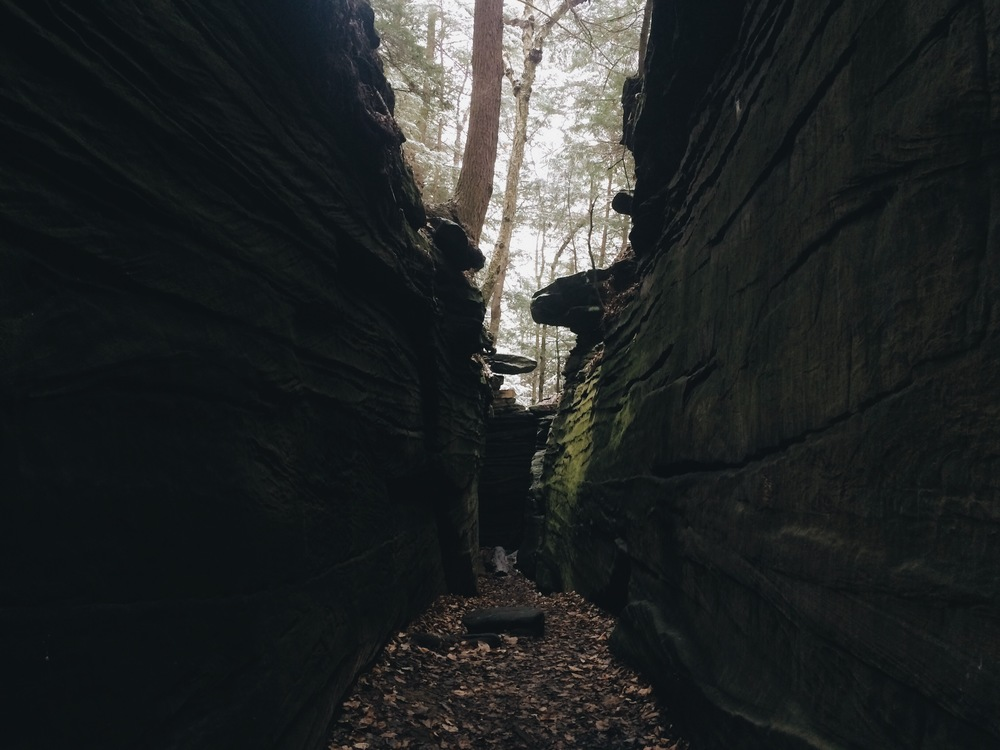 """If you ever find yourself near Akron, Ohio go to the Ledges park. Take the trail to """"Ice Box Cave"""" and once you reach the cave only discover that there is a massive fence stopping you from going inside, walk a little further. You'll find a small crevice (if you are my size) you can barely fit through. Squeeze in, and find yourself here. A rectangular, smooth, corridor that felt like something out of this world. There were several carvings (see one below, I'm keeping the others just for me) and a silence I've never experienced. Truly a hidden wonder."""