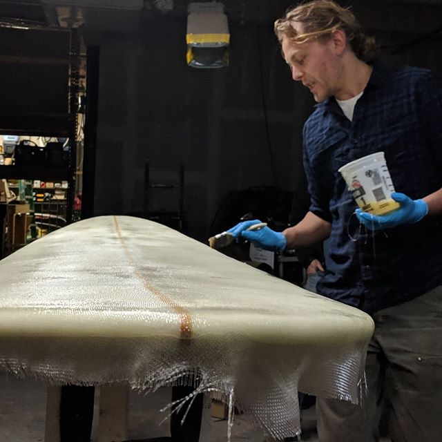 @tyler_s_a_u_t_e_r glassing a single fin he just shaped in preparation for that good winter surf.