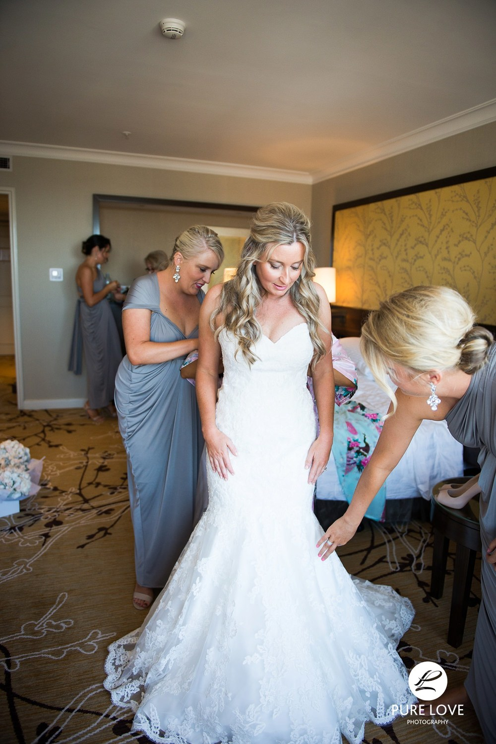 Bridesmaids helping the bride get dressed.