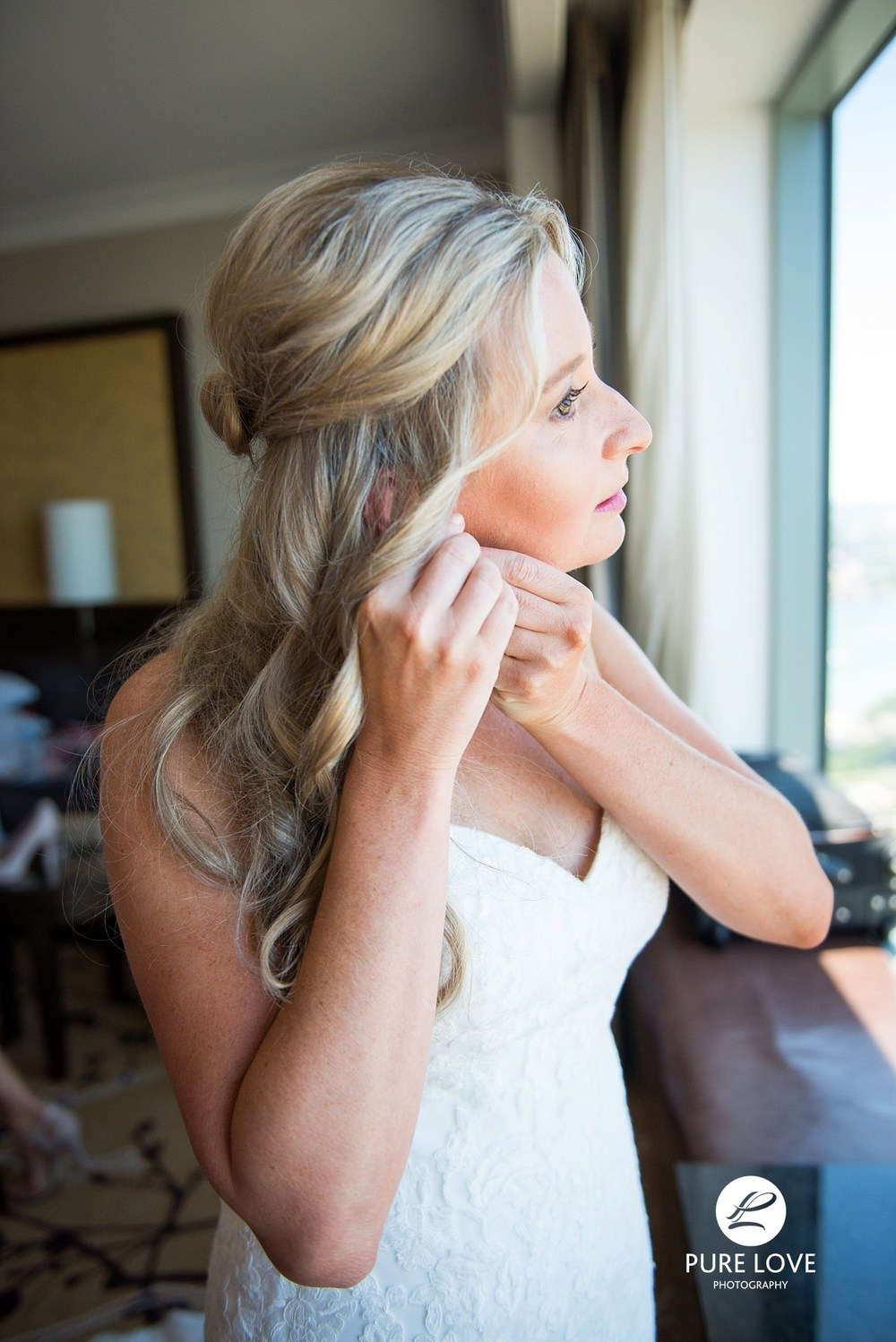 Bride is putting her earrings on. Bride's preparation. New Zealand wedding photography