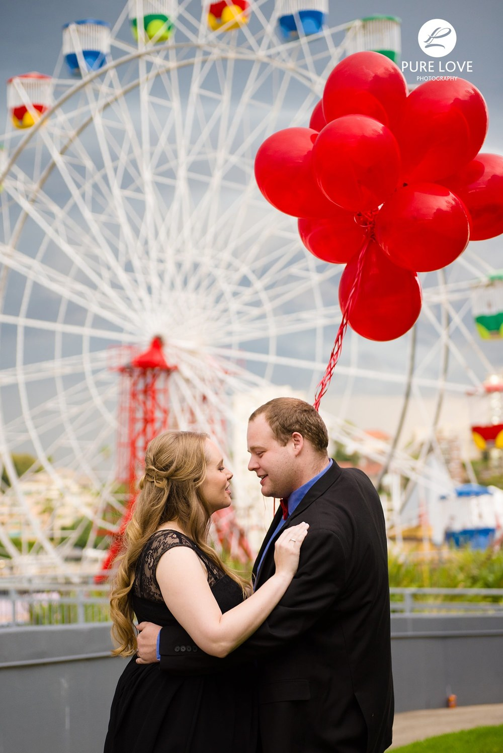 Engagement Session at Amusement Park. Ferris Wheel on the background. Kissing with balloons.