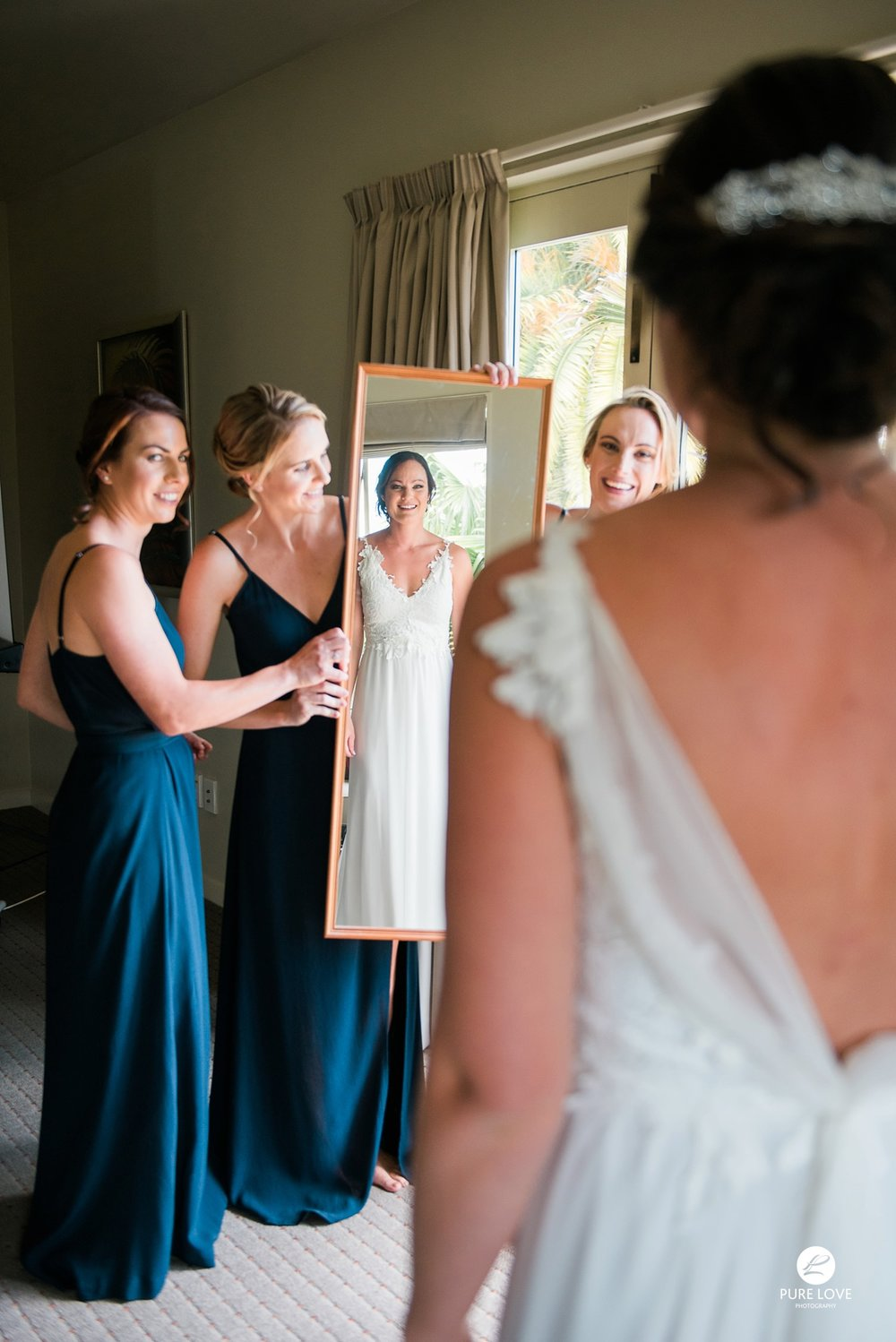 happy bride is looking into the mirror