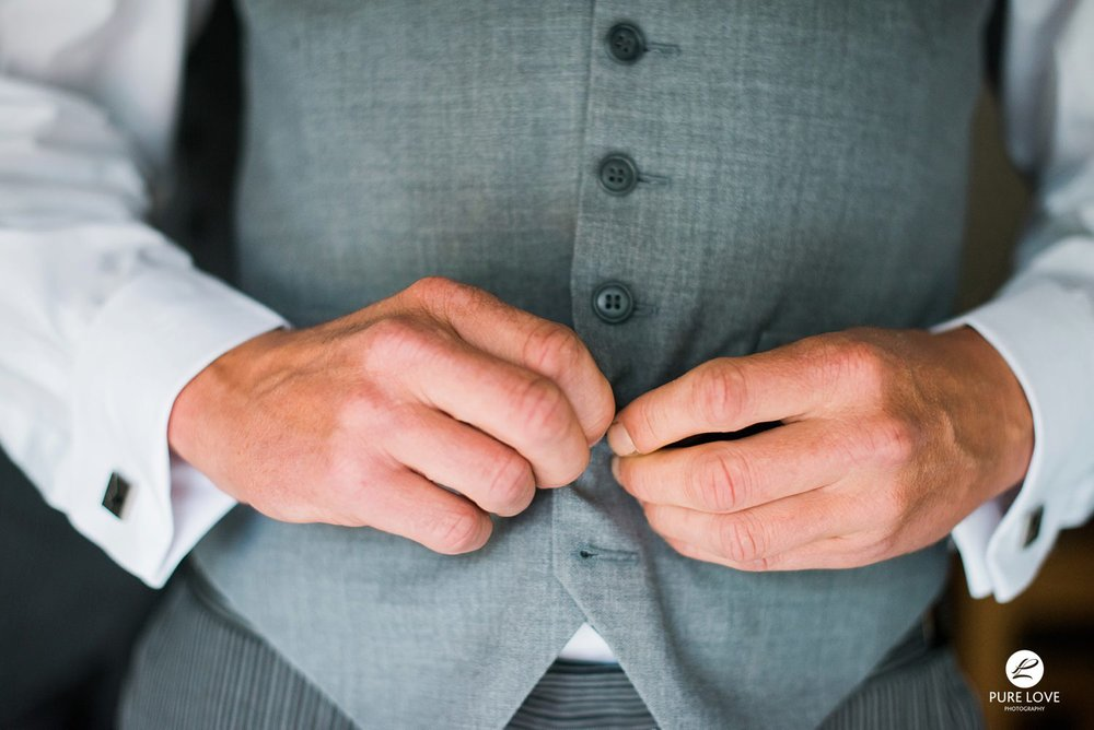 groom is buttoning his vest