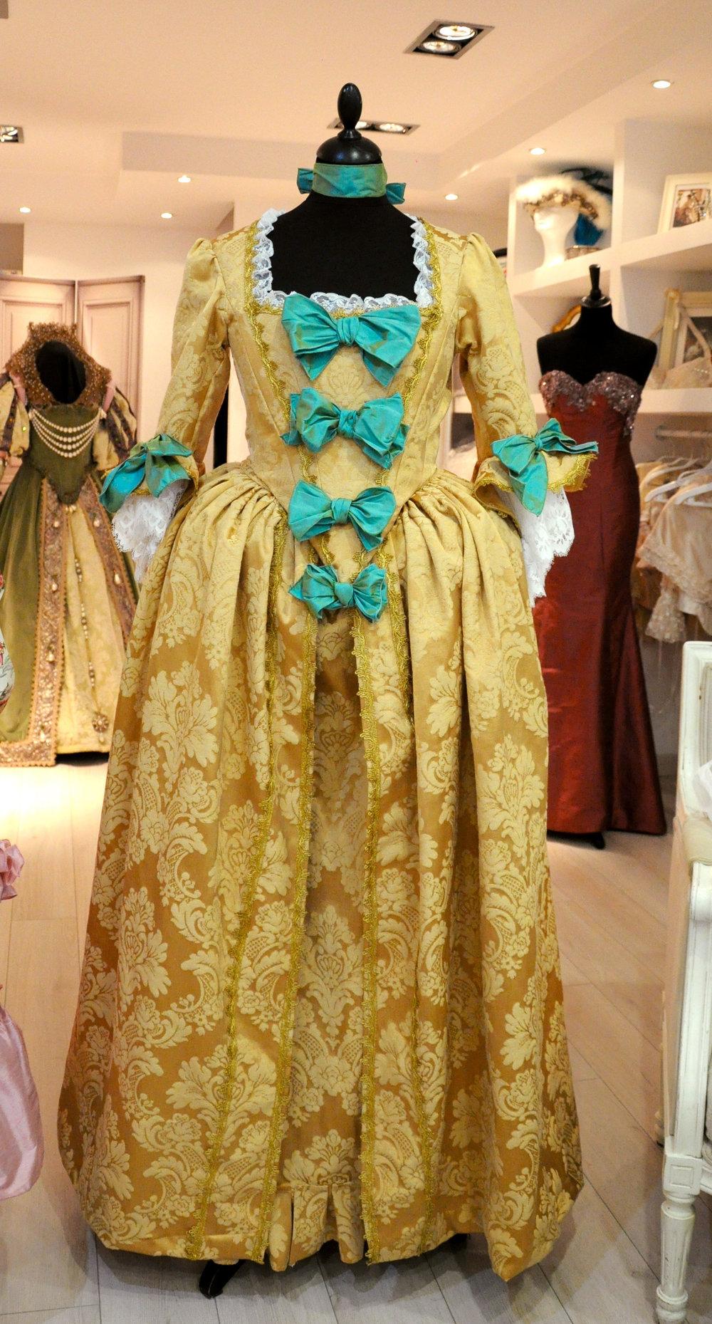 Robe XVIIIe dorée avec noeuds de soie bleue, création Agnès Szabelewski