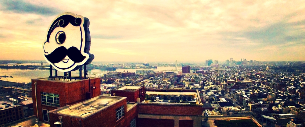 "Mr. Boh, the iconic logo of National Bohemian Beer high atop the former National Brewery, keeps an ""eye"" on Canton (foreground), the Inner Harbor (middle ground), and downtown Baltimore (background)."