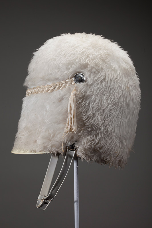 One of the hats featured in the Hats Off to Dr. Seuss Exhibition.  Made by Stanbury Co., Kansas City, of leather, plastic, metal and white fake fur. A gift from San Diego State University in 1986. Ted was chosen honorary chairman of the Holiday Bowl football game between the Iowa Hawkeyes and the San Diego State Aztecs.