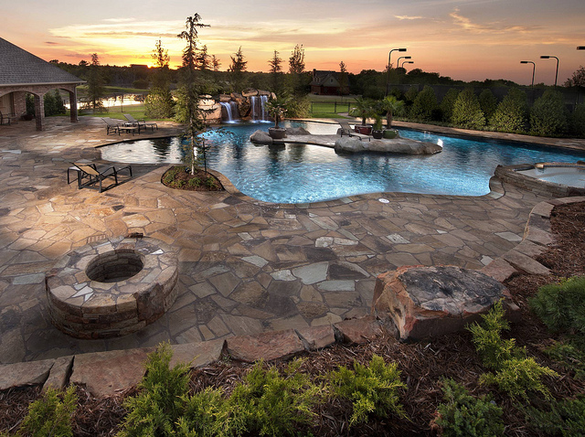 In addition to a permanent fire pit, this design includes an island living area.  Yukon Estate by   Caviness Landscape Design