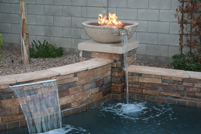 Gorgeous firewok elements compliment the clean lines of the pool.  By   Cameo Pools