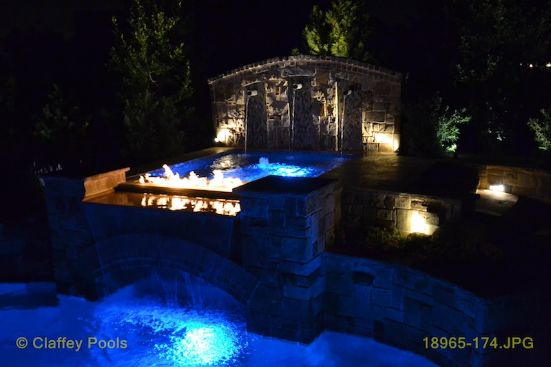 Stunning fire and water accents compliment the masonry of this installation.  By   Claffey Pools