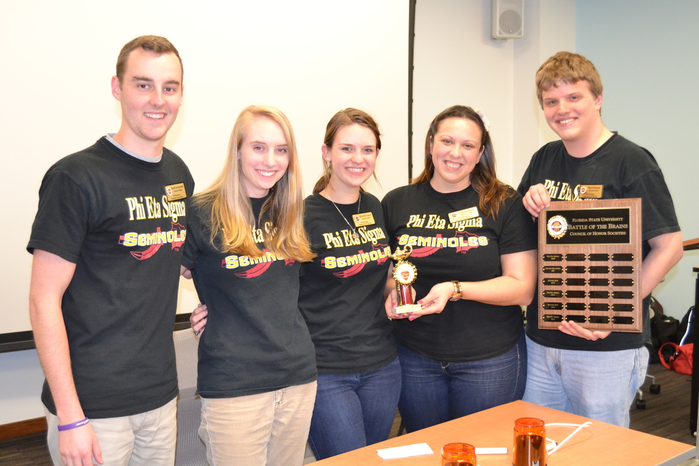 Phi Eta Sigma - Gold posing with their plaque and trophy.