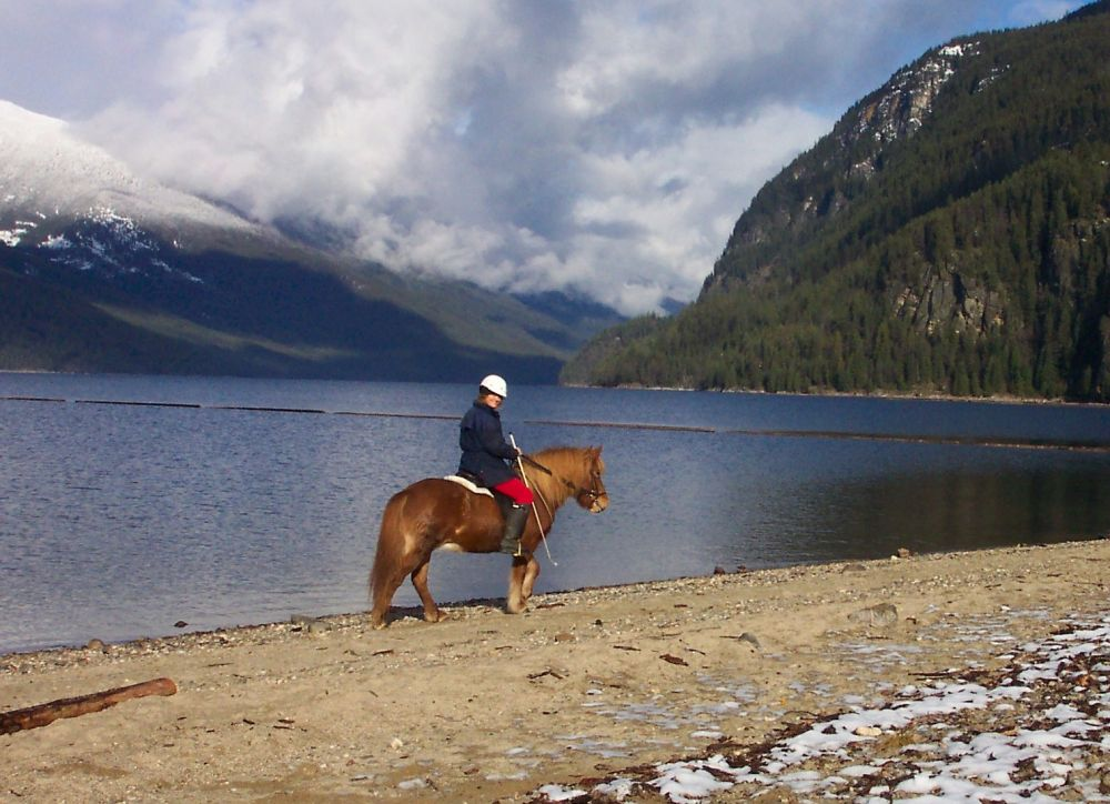Tammy riding Run along the Slocan beach