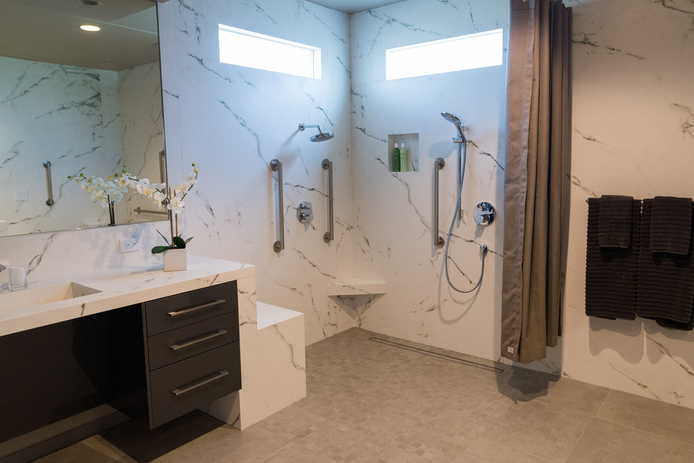 Roll in shower, heated bench (and flooring) and grab bars.