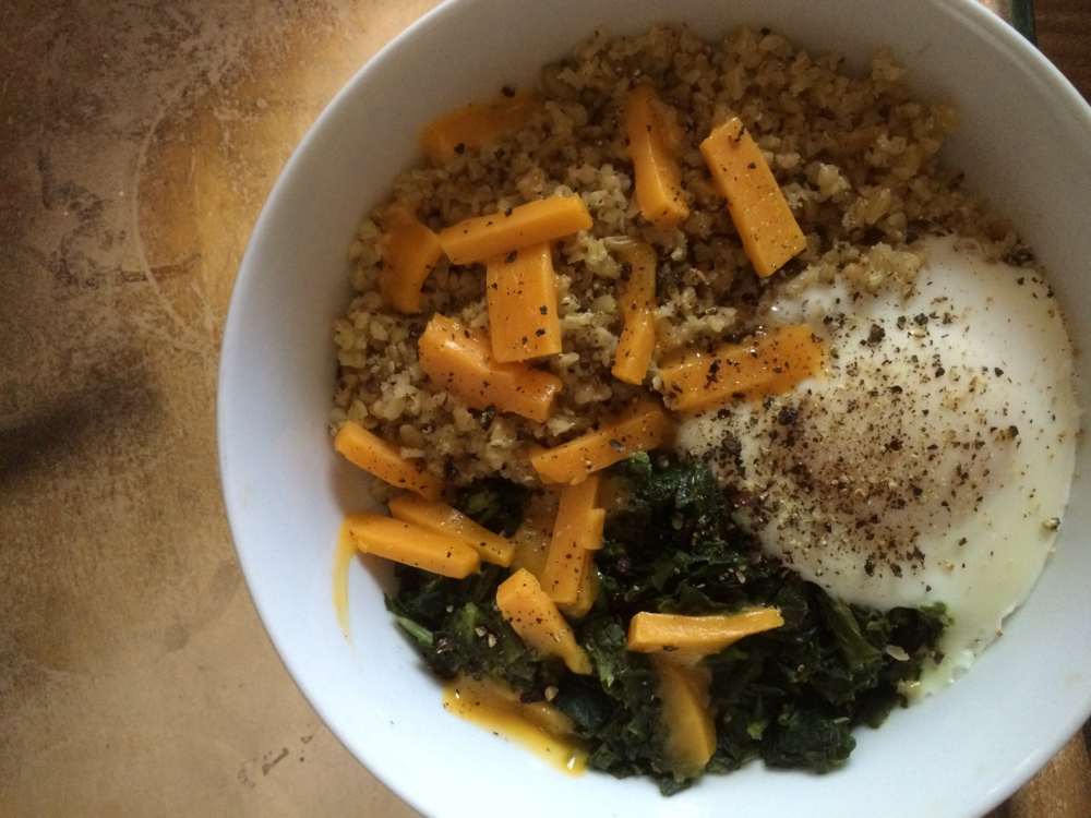 Freekeh with chopped spinach, sharp cheddar cheese, a poached egg, and cracked pepper.
