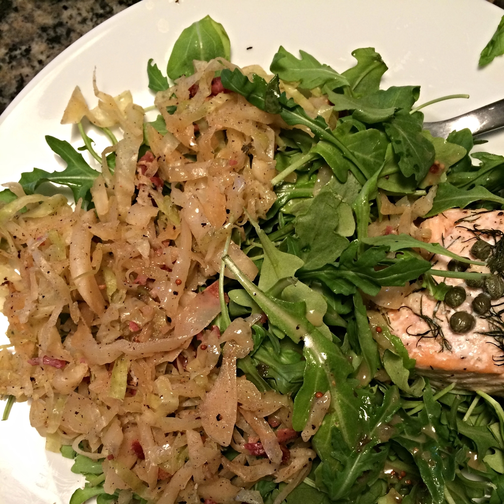 Sauteed cabbage paired with baby arugula and baked salmon.