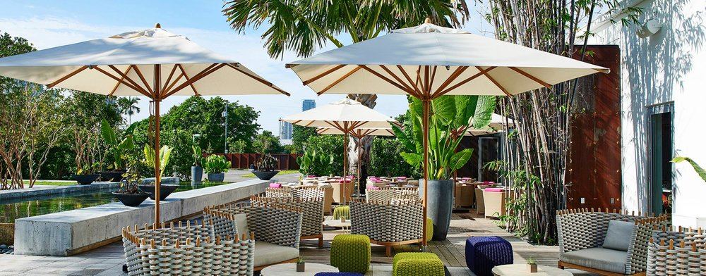 The 10' Square Levante Commercial Market Umbrella enhances the decor of this Miami hot spot.