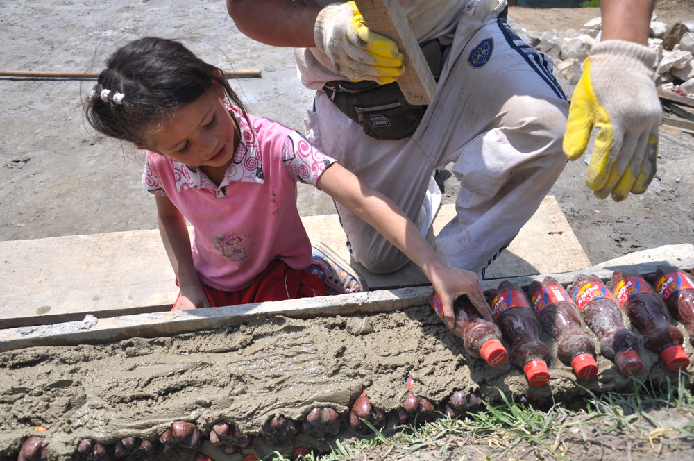The center was built with the help of the community. Here little Karina helping out in making the walls of plastic bottles filled with sand.