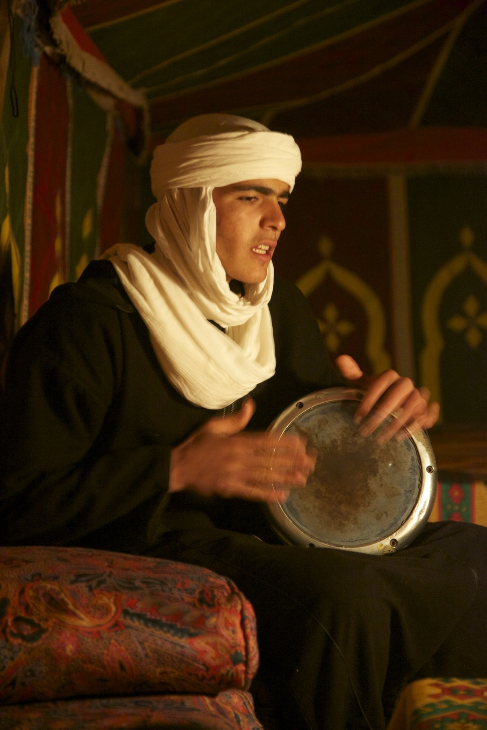 Berber guy playing a drum in the dining tent.
