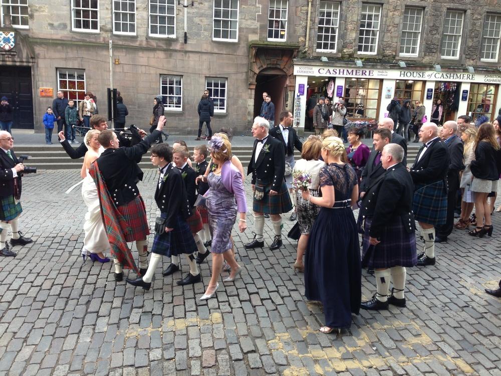 A wedding party walks along the Royal Mile. (Edinburgh, Scotland.)