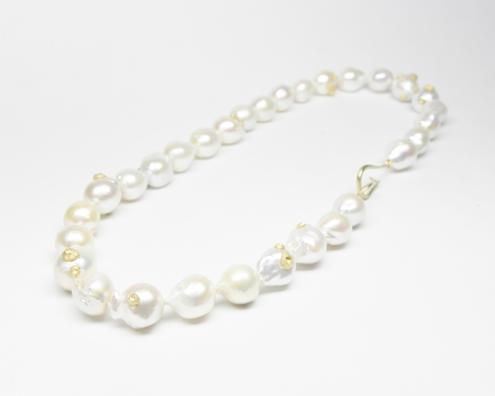 KNOTTED BAROQUE PEARL NECKLACE WITH BARNACLES   This eloquent strand of white Freshwater Baroque Pearls whisper secrets of luxury. The voluptuous beads are individually knotted, and glow with ethereal luster and charm. They are speckled with teeny tiny barnacles, perfect for mermaids and seafarers.