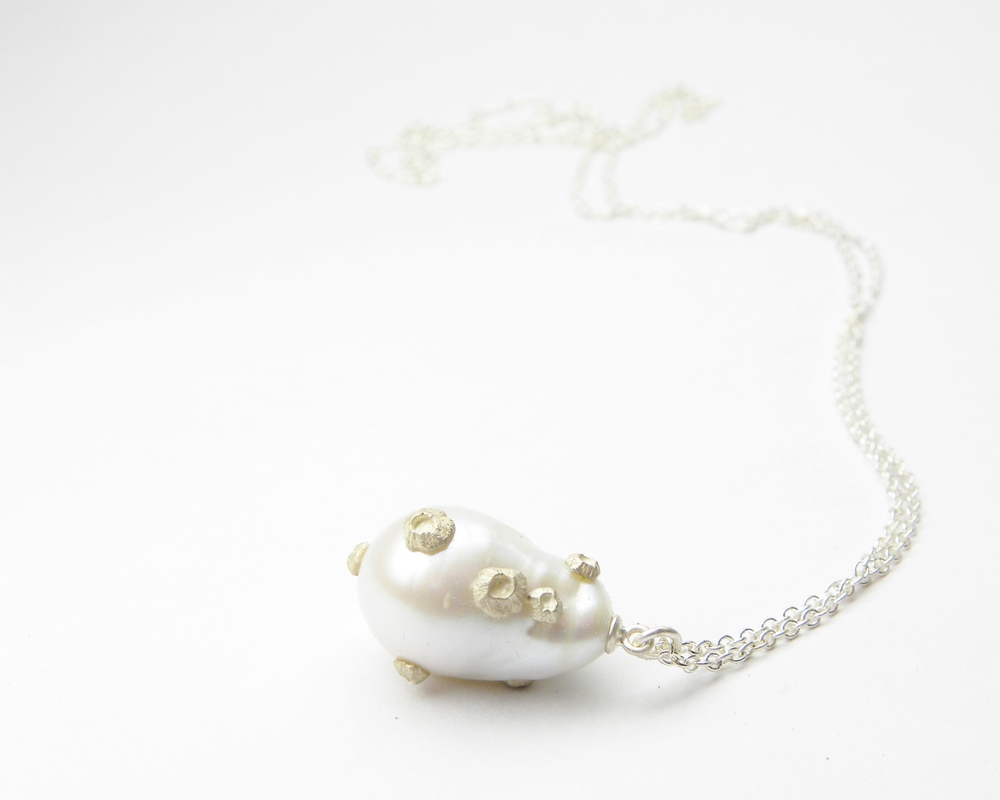 GRAND WHITE BAROQUE PEARL NECKLACE WITH BARNACLES   This unique freshwater baroque pearl is known for its irregular shape and luster. The grand pearl is decorated with teeny tiny barnacles, and hangs lavishly from its long chain.