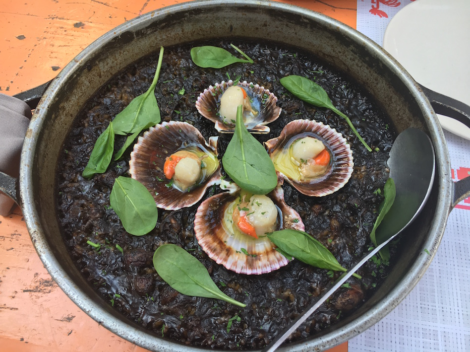 The black rice paella at Gallito is topped with baby cuttlefish and scallops.