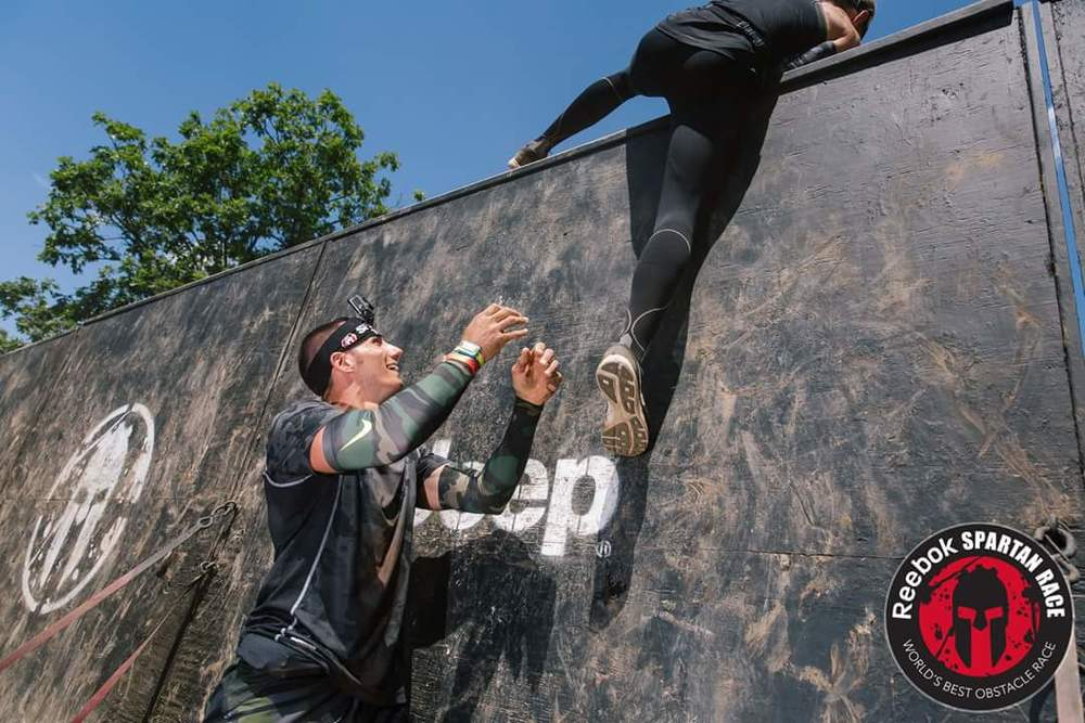 Shawn helping a team member over one-of-the many walls at Tuxedo Ridge Spartan Sprint. We conquer the course as a team, helping each other out and encouraging each other every step of the way.