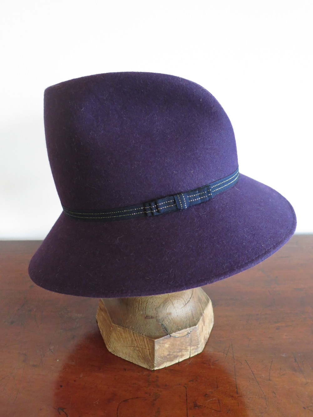 The Katie. Purple Felt in with a tall crown, dented in front. The brim can be worn down, or curved up. Accented in thin black ribbon with sliver detail.