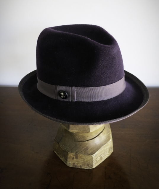 The Parker, a plum Fedora/Trilby in soft fur felt. The ribbon is adorned with a vintage button found in a flea Market in Hamburg.  D  etailed stitching on edge for an interesting effect