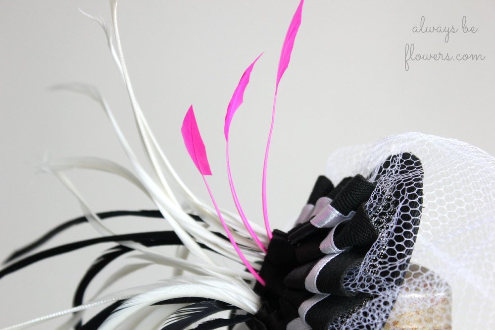 The pop of pink feathers will pull together the pink accessories she is pairing with a black and white dress.