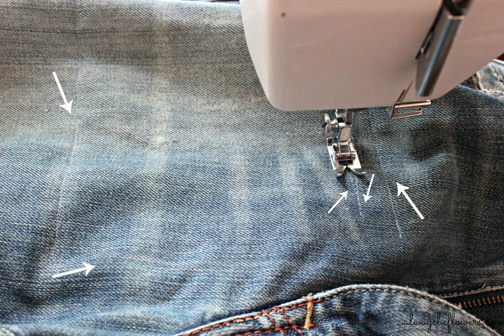 Machine sewing a denim patch to tattered jeans.