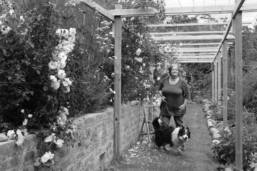 Jules, doctor in residence, taking a moment in her rose arbor with the elusive sheepdog, Monty.