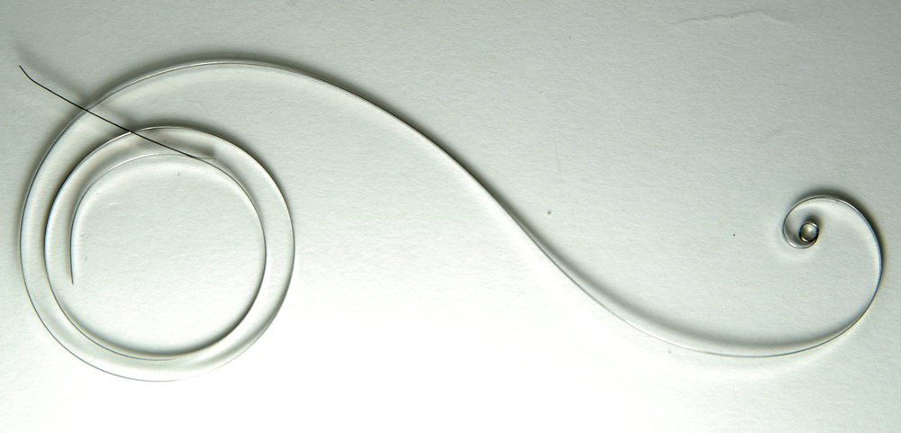 Uncoiled mainspring. Image by  Hustvedt from Wikimedia Commons