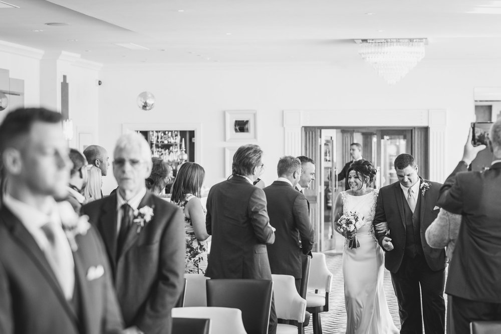 Bride and brother walk aisle