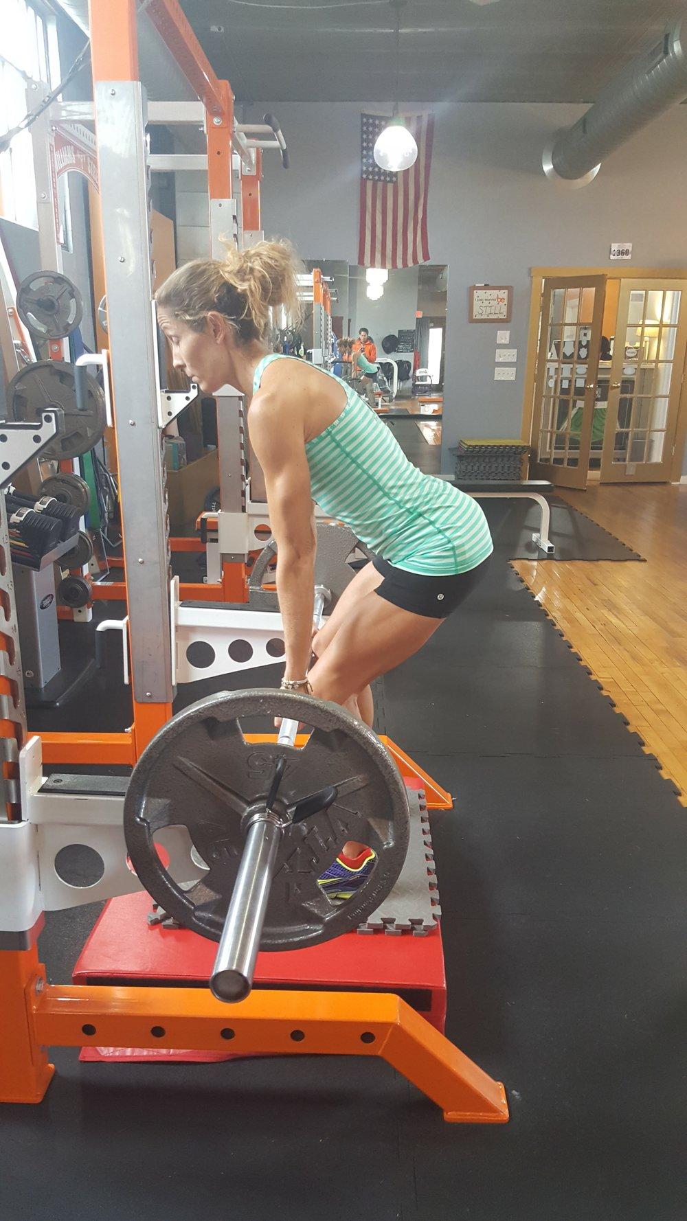 Amy performs a barbell rack lift to improve the force production of her gluteals and hamstrings.  This exercise also improves her core strength.