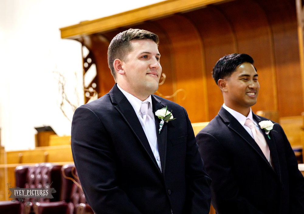 groom watching bride walk down the isle