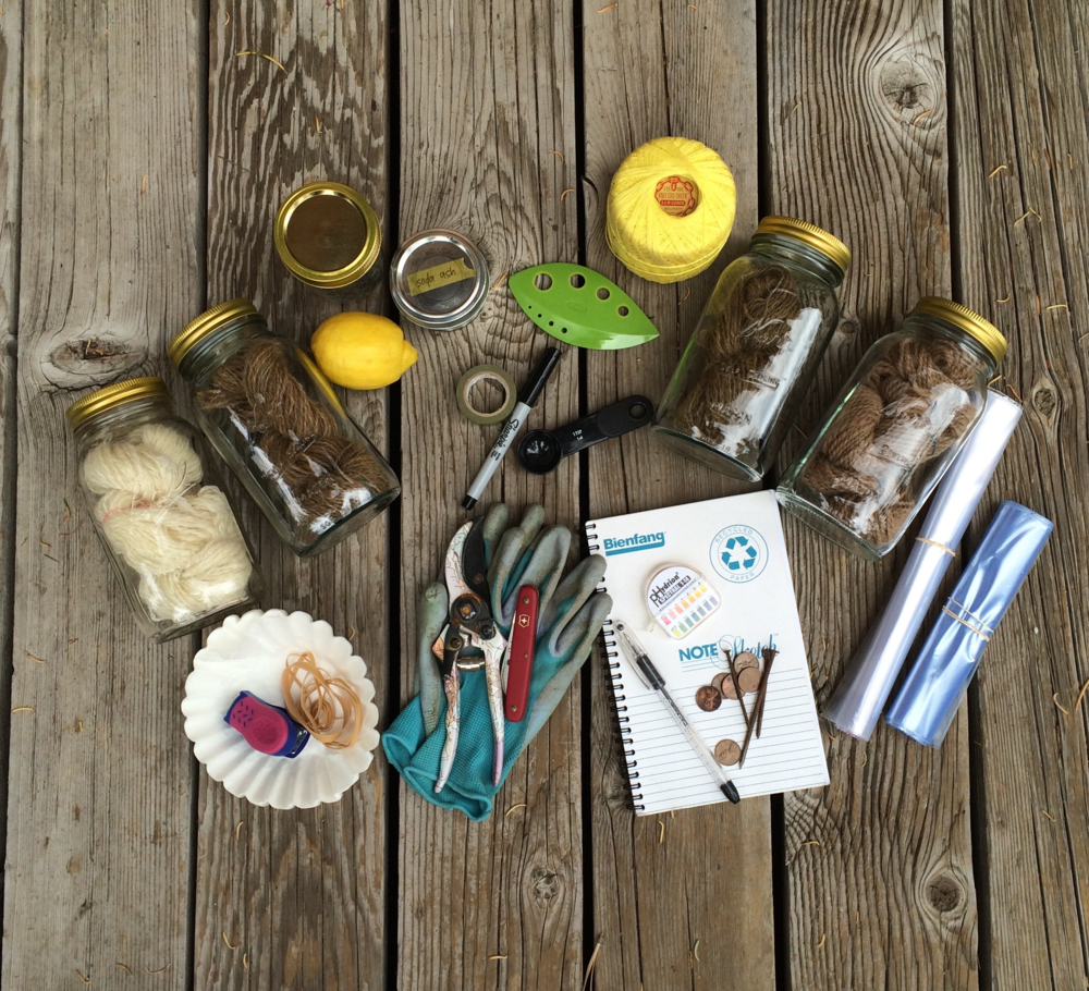 The dye kit, out of its tub. Supplies clockwise from left: alum-mordanted white hand-spun wool in its mason jar, iron-mordanted tan hand-spun wool in its mason jar, an empty mason jar for collecting wood ash from the campfire, lemon, soda ash, washi tape, sharpie, teaspoon, herb stripper, extra string, another iron-mordanted hand-spun wool, alum-mordanted tan alpaca, gallon and quart ziploc bags, notebook, pen, pH testing strips, rusty iron nails, copper pennies, pocket knife, garden shears, gardening gloves, paper coffee filters, rubber bands, and a mini stapler.