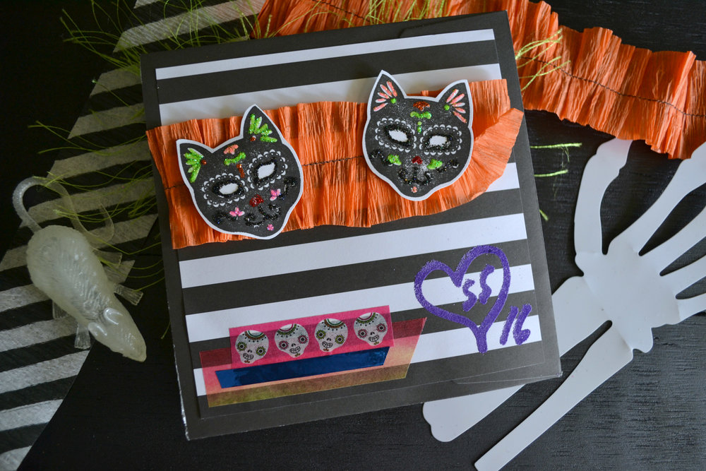 The Day of the Dead kitties are a Michaels stamp I decorated with Stickles. Also, that purple embossing powder sucks. The color completely separates when you heat it.